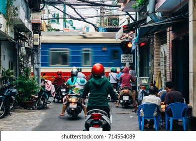 HO CHI MINH CITY, VIETNAM - JANUARY 19, 2017:  Traffic on the streets of Saigon (Ho Chi Minh) people in colorful helmets driving scooters are waiting for the train to pass.