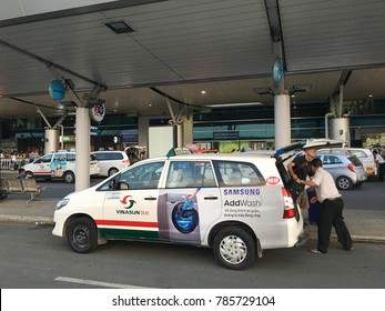 HO CHI MINH CITY, VIETNAM - DEC, 2017: A Vinasun taxi driver takes off a passenger at the Tan Son Nhat International Airport. The airport serves Ho Chi Minh City and the rest of southeastern Vietnam.