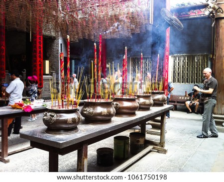 Ho Chi Minh City, Vietnam - December 15, 2013: Ba Thien Hau Temple (Pagoda), tourists with smoking prayer sticks or burning incense in copper urns, praying and taking photos in a Chinese-style temple