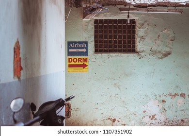 Ho Chi Minh, Vietnam - April 27, 2018: Two sheet signs (saying Airbnb and Dorm) on a dirty shabby wall with a barred window show the direction to budget rooms in backstreets of famed Bui Vien Street.