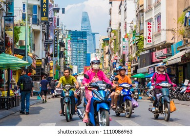 Ho Chi Minh, Vietnam - April 27, 2018: View of Bui Vien Street with its hotels' signboards, Bitexco Tower and Vietnamese people ride scooters. Famous Saigon city tourist attraction in District 1