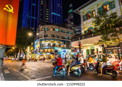 Ho Chi Minh, Vietnam - April 27, 2018: Night view of Mac Thi Buoi & Dong Khoi Streets, bikes on traffic light, restaurants, flag of Communist Party of Vietnam, Saigon Times Square Tower (blue lines)
