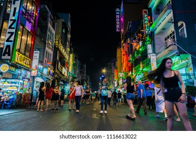 Ho Chi Minh, Vietnam - April 28, 2018: Walking Bui Vien Street at night, still not so crowded at early hours, with colorful signboards and local and foreign visitors. Nightlife attracts many travelers