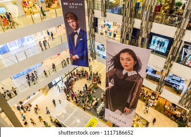 Ho Chi Minh, Vietnam - April 29, 2018: multistory interior of Saigon Centre Shopping Mall with crowds of people & 2 large ad placards (Kiton, Kimmay) showing portraits of models. Wide angle, top view