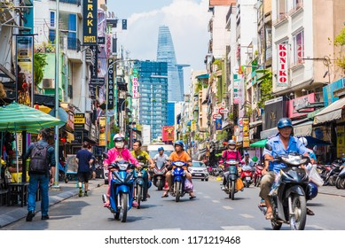 Ho Chi Minh, Vietnam - April 27, 2018: Bui Vien Street perspective, numerous signboards, people, motorbikes, Bitexco Tower. The colorful area is famous Saigon tourist attraction located in District 1.