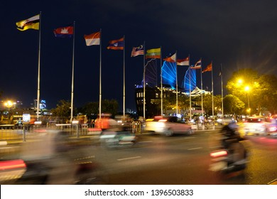 Ho Chi Minh, Vietnam - April 6, 2019: Multinational flags in ASEAN community country in the night time at Saigon with people, cars and motorcycles on the road.