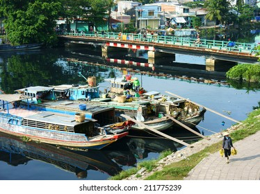 HO CHI MINH, VIETNAM- AUG 18: Scene on river, wooden boat of merchant anchor at polluted canal, bridge and boat reflect on water, residential along ditch, woman walk on street, Vietnam, Aug 18, 2014