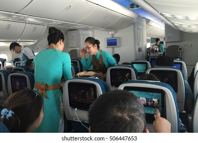 Ho Chi Minh, Vietnam - Dec 14, 2015: Vietnamese stewardess servants of Vietnam Airlines carrier serving fast food for lunch on a commercial flight from Hanoi capital to Ho Chi Minh City.