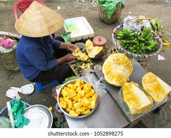 HO CHI MINH, VIETNAM - DECEMBER 14, 2013: Woman vendor cleaning jack fruit and preparing it for sale in the local market near Ho Chi Minh city
