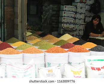 HO CHI MINH, VIETNAM - DECEMBER 14, 2013: female vendor waiting to sell sacks of legumes and grains in Vietnamese street market