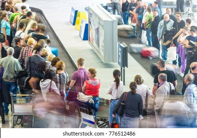 Ho Chi Minh, Vietnam - December 7, 2012: people getting luggage from conveyor belt at airport after flight. Line of passengers taking their suitcases at baggage claim area