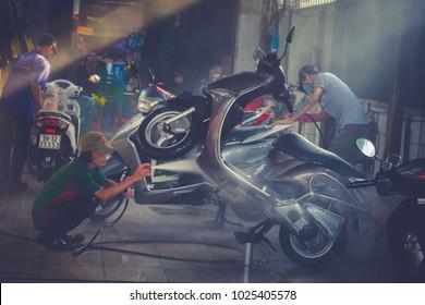 HO CHI MINH / VIETNAM - FEB 14, 2018: Men are washing motorbikes in lunar new year.