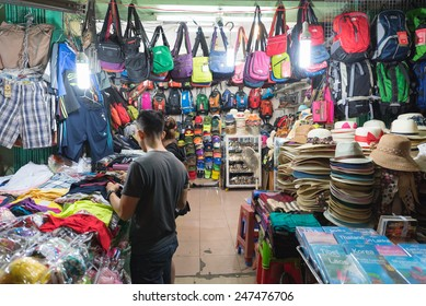 HO CHI MINH, VIETNAM - JAN 15, 2015: An unidentified man chooses wear at the Ben Thanh night market. It is popular among tourists as one can buy here various goods especially local souvenirs.
