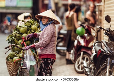 HO CHI MINH, VIETNAM - JAN 15, 2016: the Vietnamese woman sells cocoes on the street in Hochiminh (Saigon) on the sunset. Saigon is the largest city in Vietnam