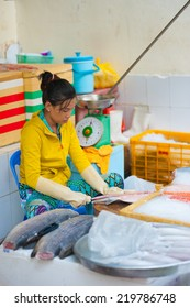 HO CHI MINH, VIETNAM - JULY 5, 2014:  An unidentified young woman at Ben Thanh market cuts a fresh salmon for sale. While tourists search here souvenirs townspeople come to buy fresh food.