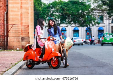 """HO CHI MINH, VIETNAM - NOV 15, 2016: Vietnamese girl traditional dress, """" Ao dai """" is famous traditional costume for woman in Vietnam. With Antique motorcycle. Near Notre Dame Cathedral."""