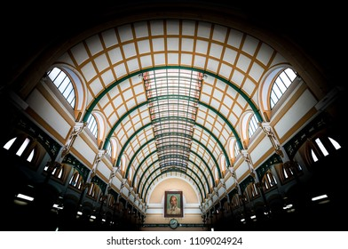 Ho Chi Minh, Vietnam - November 27, 2012: High arched ceiling of post office. Famous building in Asia. Geometric design of house. Wall with portrait, diminishing roof with windows.