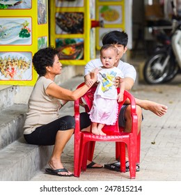 HO CHI MINH, VIETNAM - SEP 20, 2014: Unidentified Vietnamese family with a little baby on the chair. 90% of Vietnamese people belong to the Viet ethnic group