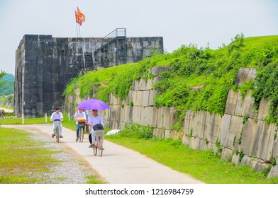 Ho Citadel, Thanh Hoa Province, Vietnam - May 9, 2014. Schoolchildren cycling home past the south wall of the Ho Citadel, which became a UNESCO World Heritage Site in 2011.