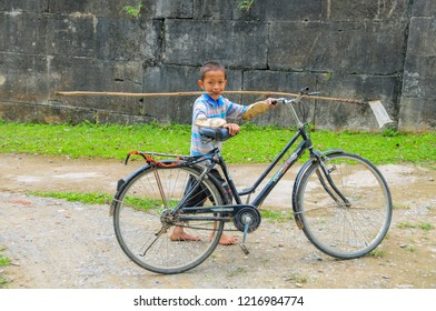 Ho Citadel, Thanh Hoa Province, Vietnam - May 9, 2014. Boy passing the north wall of the Ho Citadel, carrying stick for catching butterflies. The citadel became a UNESCO World Heritage Site in 2011.
