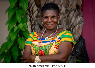 Ho, Ghana, September 16, 2018: An African woman dressed in a colorful dress smiles for the the camera.