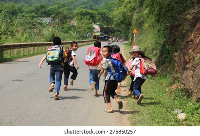 Hoa Binh, Vietnam - May 6, 2015: Young Vietnamese pupils walking home on a country road of Luong Son district after school. It's dangerous for children to join the traffic after school in Vietnam.