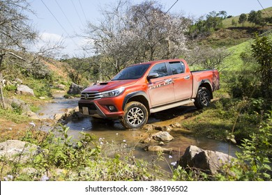 Hoabinh, Vietnam - Jan 10, 2016: The red New Toyota Hilux 2015 double cab 4x4 pickup truck crossing river and running on the mountain road in Vietnam. Japan-based car brand.