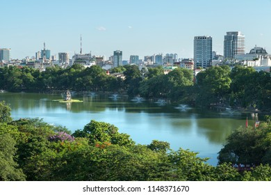 Hoan Kiem lake or Sword lake, Ho Guom in Hanoi, Vietnam with Turtle Tower, green trees and buildings on horizon