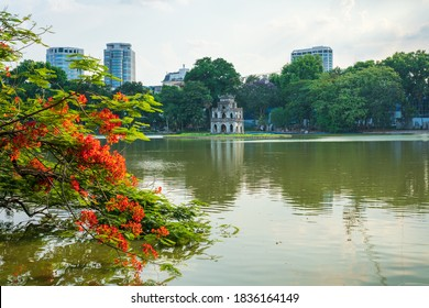 Hoan Kiem lake with Turtle Tower and flamboyant flowers on foreground in Hanoi, Vietnam.