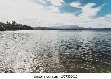HOBART, AUSTRALIA - September 9th, 2019: view of Conningham Beach in Tasmania with its pristine rugged coastal beauty and the typical colorful beach huts in the distance