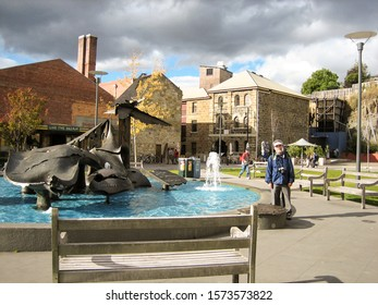 HOBART, AUSTRALIA-APR. 11, 2006:  A tourist stands near a marine sculpture in the city's Salamanca Square, the historical and cultural hub of the city.