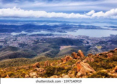 Hobart city from elevation of Mt Wellington on shores of Derwent river around Sullivan's cove on a cloudy day - scenic nature of Tasmania.