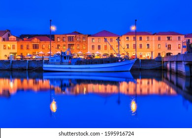 Hobart city harbour named Sullivans cove at sunset with bright illuminated waterfront of historic buildings along pier with fishing boat reflecting in still waters.