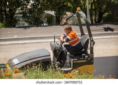 Hobart, Tasmania, Australia, November 4, 2020: Male worker sitting on a heavy road roller just after fresh bitumen has been layed on a suburban sidestreet near Hobart