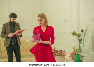 Hobby concept. Happy woman hold flower in pot while hipster reading book, hobby. Indoor gardening as hobby. Enjoy family hobby activities.
