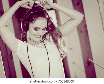 Hobby music expression and free time. Young girl listen music dance with hands in air above head.