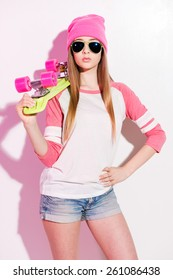 A hobby and a passion.  Playful young woman in pink headwear and sunglasses holding skateboard on her shoulder while standing against white background