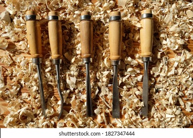 hobby toll chisels on the carpenter's workbench, chisel in the yellow waad sawdust, chisel on the presentation board, wood hobby tools