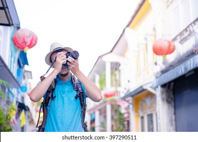 Hobby and travel. Young man with backpack taking photo with his camera on asian street.