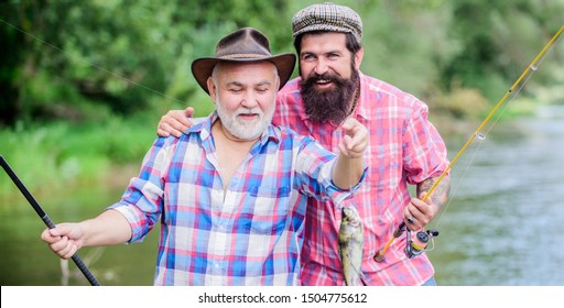 hobby unites. hunting tourism. father and son fishing. Big game fishing. friendship. two happy fisherman with fishing rod and net. Camping on the shore of lake. Fly Fishing Time. hobby.