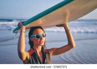 Hobby and vacation. Holiday on the beach. Pretty young woman carrying surf board.