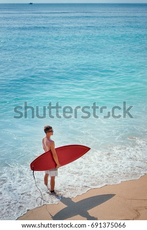 f7b820db917 Hobby and vacation. Holiday on the beach. Young man carrying surf board.