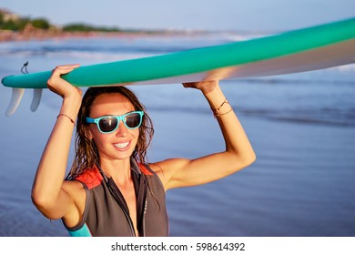 Hobby and vacation. Portrait of surfer. Happy young woman carrying surfboard on the sea beach.