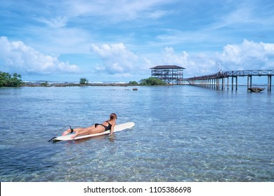 Hobby and vacation. Sunny holiday on the beach. Young surfer woman surfing having fun on Cloud Nine Spot, Siargao Beach, Philippines.