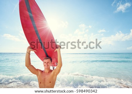 50c45422047 Hobby and vacation. Sunny holiday on the beach. Young man carrying surf  board.