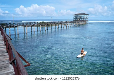 Hobby and vacation. Woman swimming over surfboard in clear blue water at  beach, Siargao Island, Philippines.