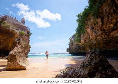 Hobby and vacation. Young man with surfboard on beautiful beach with high rocks. Uluwatu spot, Bali island, Indonesia.