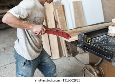 Hobby wood concept. Profile side view cropped photo of cabinetmaker handcraft mature man push wooden plank board on saw table with special protection tool