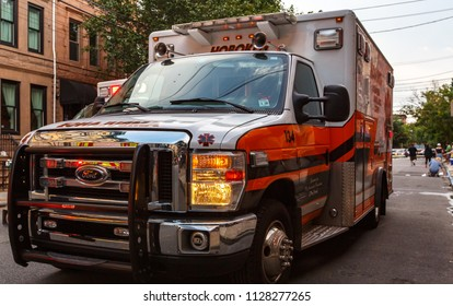 Hoboken, New Jersey / USA - 06 26 2018: EMS ambulance car stay on street in daytime, townhouses around.