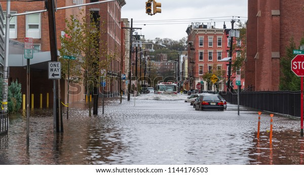 Hoboken, New Jersey / USA - 10302012: Superstorm Sandy Hoboken, NJ. Flooded streets and cars at the corner of Willow ST and 4th ST. Fire truck plowing through.